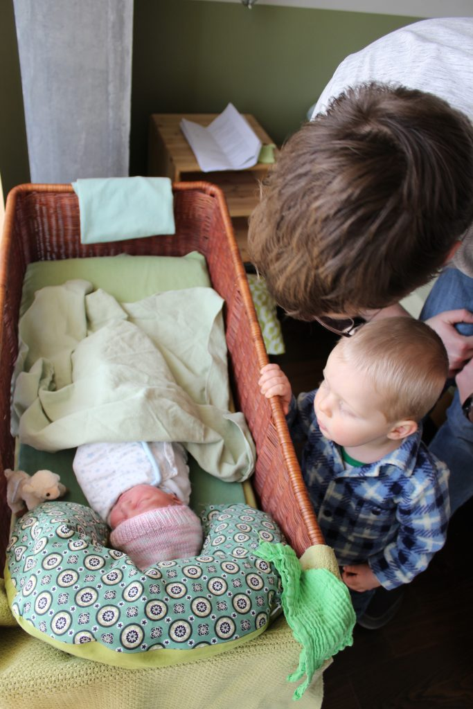 Big brother observes newborn baby sister