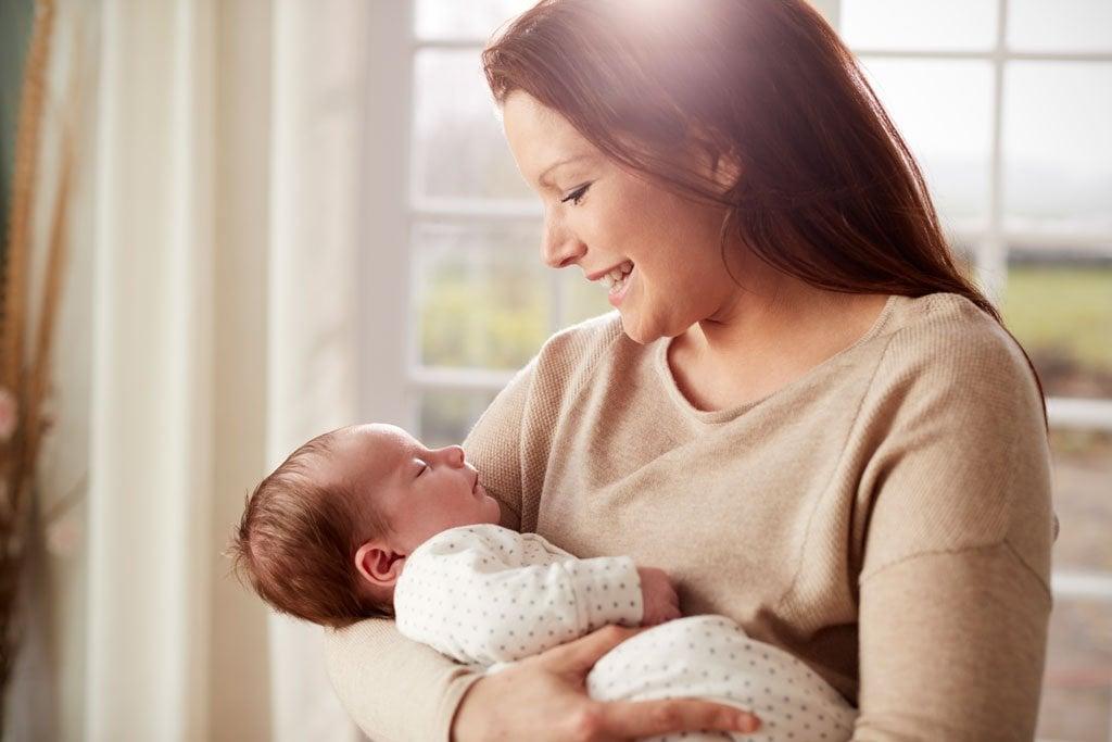loving mother cuddling newborn